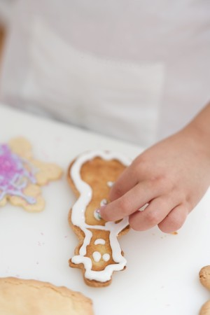 silver balls: Child decorating Christmas biscuit with silver balls