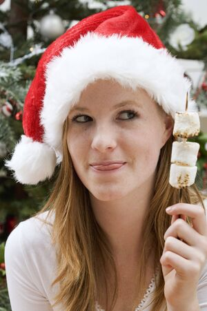 25 to 30 year olds: Woman in Father Christmas hat holding marshmallow skewer