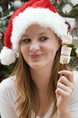 25 to 30 year olds: Woman in Father Christmas hat holding marshmallows on stick LANG_EVOIMAGES