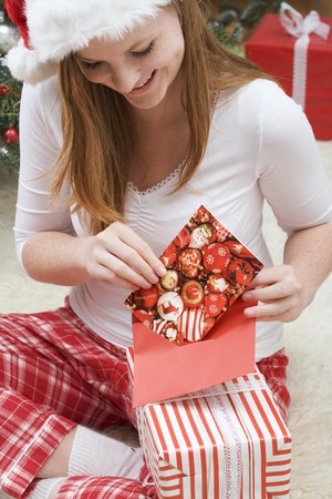25 to 30 year olds: Woman in Father Christmas hat putting Christmas card into envelope
