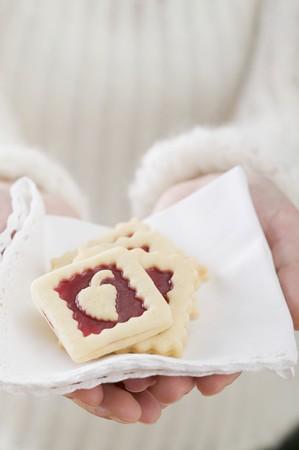 jam biscuits: Donna azienda marmellata biscotti su tessuto tovagliolo