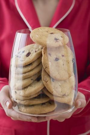 vaccinium macrocarpon: Woman holding glass full of cranberry cookies