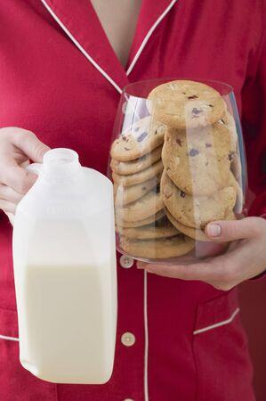 vaccinium macrocarpon: Woman holding glass full of cranberry cookies & bottle of milk