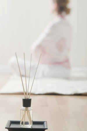incense sticks: Incense sticks with scented oil, woman sitting cross-legged