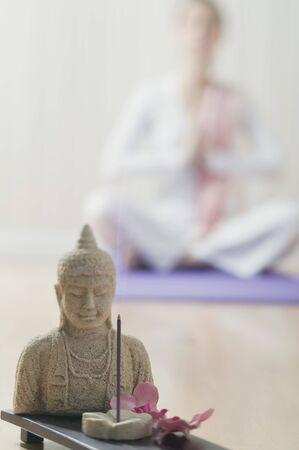 incense sticks: Buddha statue & incense sticks, woman sitting cross-legged