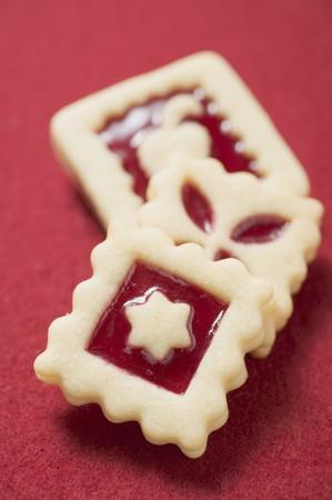 jam biscuits: Tre marmellata biscotti quadrati su sfondo rosso