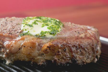 qs: Beef steak with herb butter on barbecue (close-up)