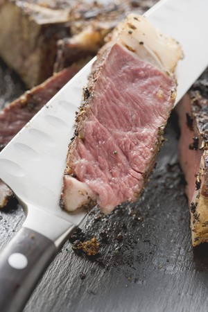 rib eye: Slice of spicy rib eye steak on knife (close-up) LANG_EVOIMAGES