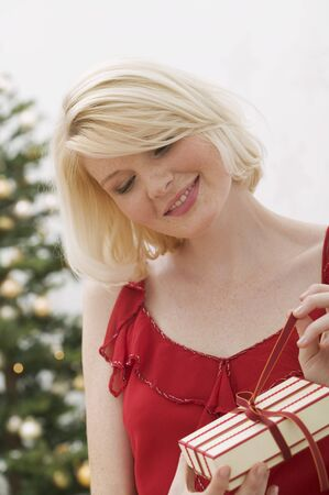 25 to 30 year olds: Woman opening Christmas parcel LANG_EVOIMAGES