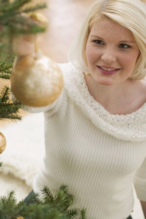 25 to 30 year olds: Woman hanging gold bauble on Christmas tree