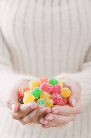 sugarcoated: Hands holding coloured sugar-coated jelly sweets