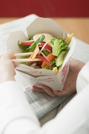 well beings: Woman eating Asian vegetable dish out of take-away container LANG_EVOIMAGES