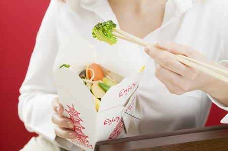 low blouse: Woman eating Asian vegetable dish out of take-away container LANG_EVOIMAGES