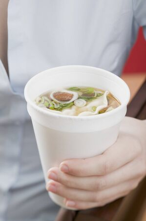 asian noodle: Woman holding paper cup of Asian noodle soup LANG_EVOIMAGES