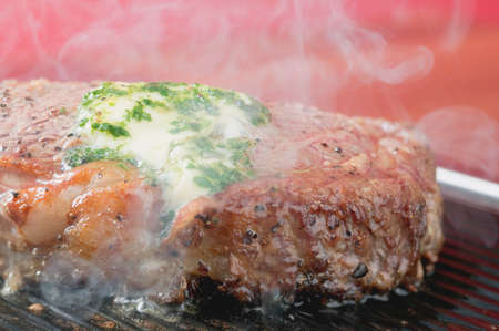 barbecues: Steaming beef steak with herb butter on barbecue