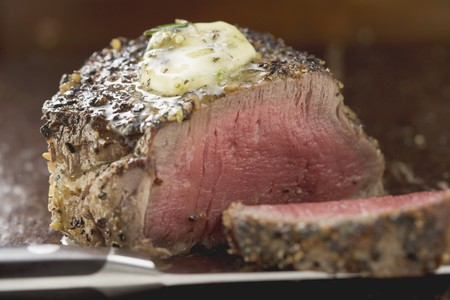peppered: Peppered steak with herb butter, a slice cut off LANG_EVOIMAGES