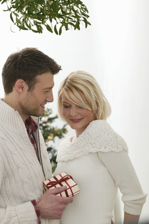 25 to 30 year olds: Man giving woman Christmas gift under mistletoe