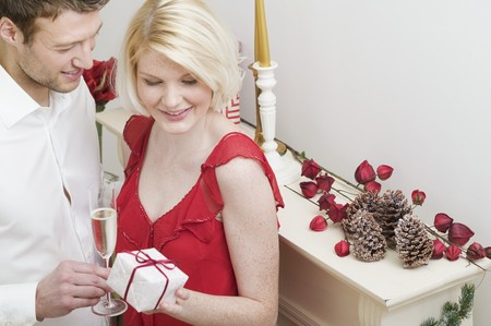 mantelpiece: Man giving Christmas gift to woman by fireplace LANG_EVOIMAGES