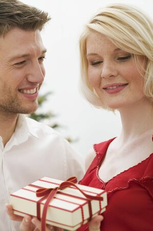 25 to 30 year olds: Man giving Christmas gift to woman