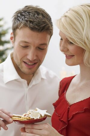 25 to 30 year olds: Woman offering man Christmas biscuits