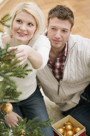 decorating christmas tree: Couple decorating Christmas tree