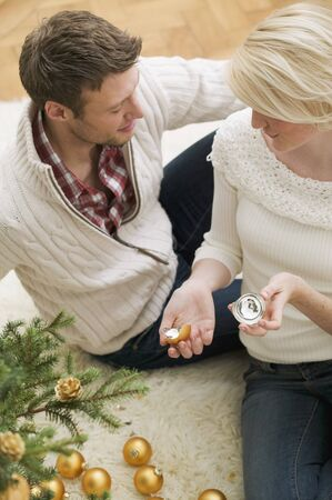 25 to 30 year olds: Couple beside Christmas tree, woman holding broken bauble