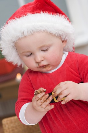 eat smeared: Baby in Father Christmas hat, messy with chocolate