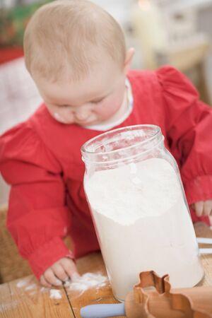12 step: Toddler putting flour on wooden board LANG_EVOIMAGES