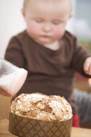 12 step: Toddler sprinkling sugar on almond cake