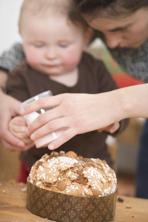 12 step: Mother and toddler sprinkling sugar on almond cake