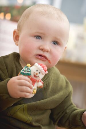 smeared baby: Baby holding Christmas biscuit (bitten) LANG_EVOIMAGES