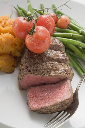 qs: Beef steak, a slice cut off, with cherry tomatoes