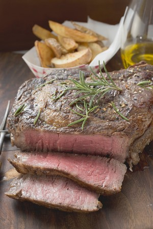 sirloin steak: Sirloin steak, partly sliced, potato wedges in background