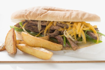 hero sandwich: Steak and cheese sandwich with potato wedges LANG_EVOIMAGES