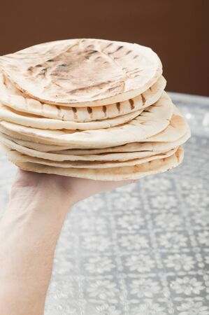 qs: Hand holding stack of grilled flatbread