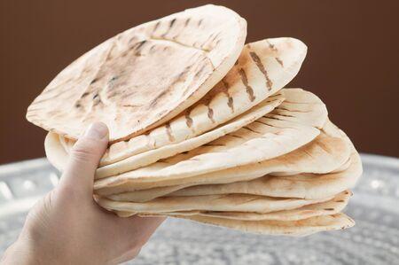 several breads: Hand holding several grilled flatbreads LANG_EVOIMAGES