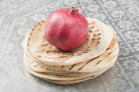 qs: Pomegranate on a stack of flatbread