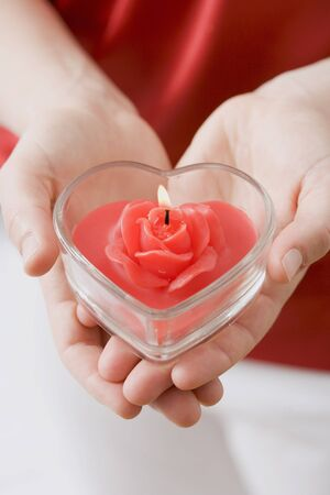 ignited: Hands holding heart-shaped windlight with rose candle