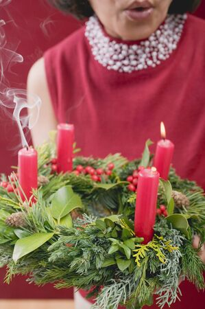 blowing out: Woman blowing out candles on Advent wreath LANG_EVOIMAGES