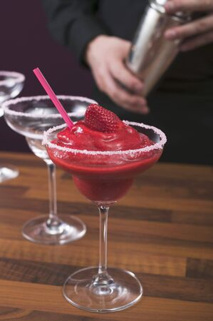 barkeep: Strawberry Daiquiri in glass, bartender in background LANG_EVOIMAGES