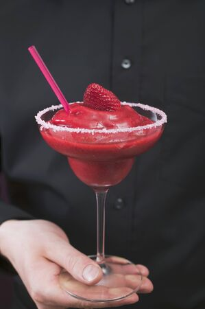 Man holding a glass of Strawberry Daiquiri