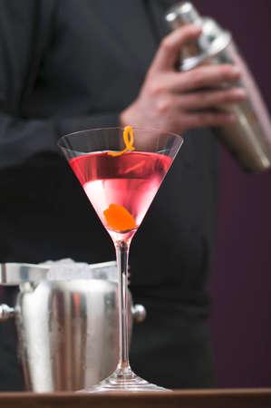 barkeep: Cosmopolitan in glass, bartender with cocktail shaker LANG_EVOIMAGES