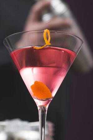 Cosmopolitan in glass, bartender in background