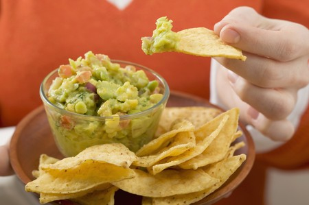 nacho: Woman dipping nacho in guacamole LANG_EVOIMAGES