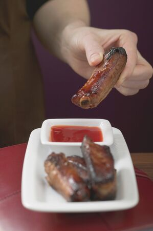 pork rib: Donna che tiene vetrata costola di maiale su salsa di peperoncino
