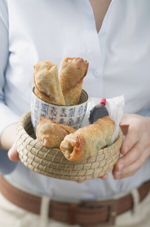 waist deep: Woman holding basket of spring rolls and soy sauce