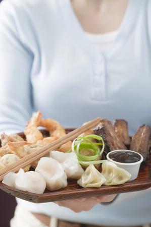 waist deep: Woman holding Asian appetiser platter LANG_EVOIMAGES