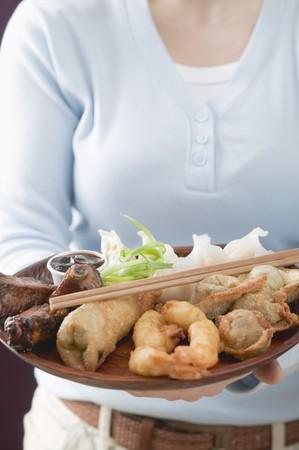 appetiser: Woman holding Asian appetiser platter LANG_EVOIMAGES