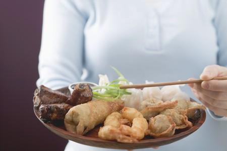 waist deep: Woman holding Asian appetiser platter and chopsticks