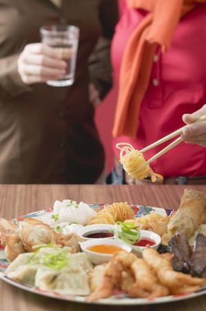 waist deep: Two women with Asian appetiser platter LANG_EVOIMAGES